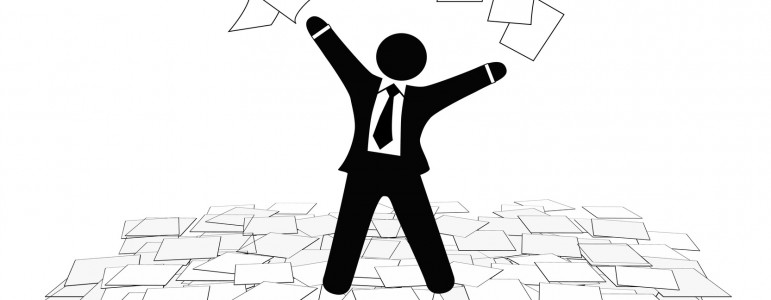 A business man throws office paper work pages into air and on floor.